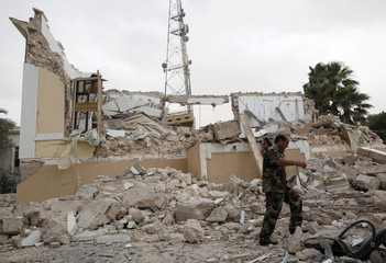 A soldier passes a government building which was damaged by coalition air strikes, according to the government, in Tripoli