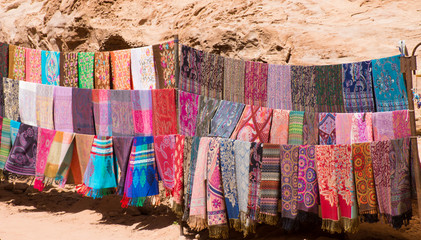 Colorful scarves or pashminas at an outdoor souvenir stand in Petra Jordan. Woven scarves and shawls have multiple designs and patterns in a rainbow of colors.