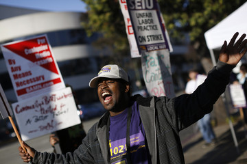 A demonstrator chants from a picket line in support of the Bay Area Rapid Transit (BART) workers strike in Oakland