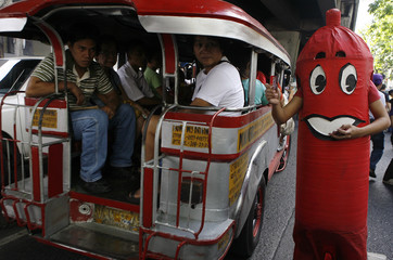 A reproductive health advocate distributes condoms to passengers in Manila