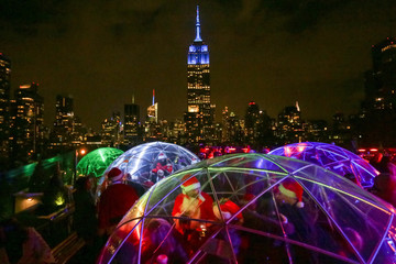 The Empire State Building is seen in the background as revellers take part in the annual SantaCon event in Manhattan, New York