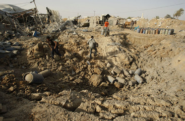 Palestinians survey the damage at the site of an overnight Israeli air strike on a smuggling tunnel in Rafah in the southern Gaza Strip