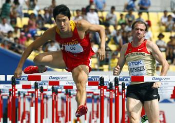Liu Xiang of China clears a hurdle next to Willi Mathiszik of Germany during their men's 110 metres hurdles heats in Daegu