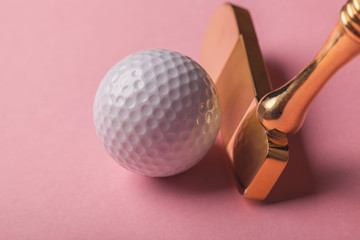 head of luxury golden golf club near golf ball on pink background