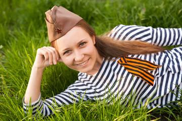 Girl in uniform of the Great Patriotic War. Warrior sitting on the grass between flowers. Girl wearing green costumes of World War II
