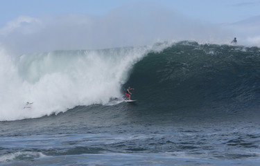 """Two surfers ride large wave as another paddles over it at surf spot on outer reefs known as """"Himalayas"""" on North Shore of Oahu in Haleiwa, Hawaii."""