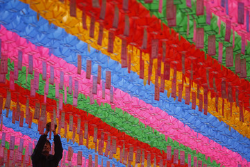 A worker attaches prayer petitions, with names written on cards, to lotus lanterns in preparation for the upcoming birthday of Buddha at Jogye temple in Seoul