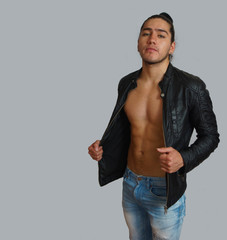 Young hispanic man with gathered hair done bow in black leather jacket without shirt, with his hands stretching his jacket, looking towards the camera