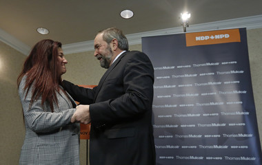 NDP leader Mulcair embraces Independent MP Mourani during a news conference in Ottawa