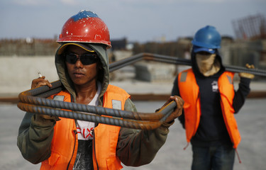 Workers carry steel bars at the construction site of a new pier at New Priok container terminal in north Jakarta