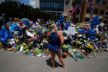 A woman pays her respects at a makeshift memorial at Dallas Police Headquarters following the multiple police shootings in Dallas