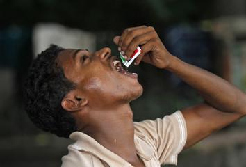 A man eats gutka along a street in Kolkata
