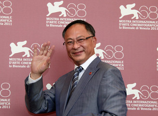"Director Johnnie To waves during a photocall for his film ""Duo Mingjin"" at the 68th Venice Film Festival"