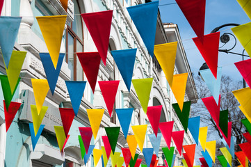 Decorative multi colored triangle flags against the background of city