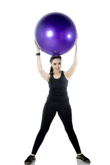 Young woman lifting fitness ball