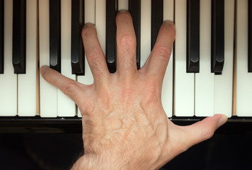 Pianist hand playing a chord.