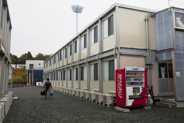 A worker walks among temporary housing structures at J-Village near TEPCO's Fukushima Daiichi Nuclear Power Plant