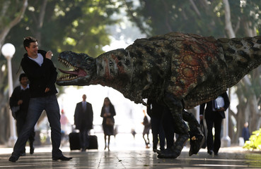 A man reacts as a performer dressed in a Tyrannosaurus rex dinosaur costume walks next to him during a publicity event in central Sydney