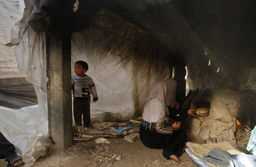 A Palestinian woman bakes bread in a wood-fired oven inside her tent in the northern Gaza Strip