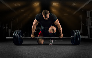 Athlete is standing on his knee and near the bar and is preparing to make a deadlift