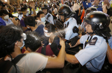 Protesters are pepper sprayed by riot police during a confrontation at Mongkok shopping district in Hong Kong