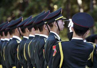 A soldier reacts as a string is used to ensure that members of the honour guard are standing in a straight line ahead of a welcoming ceremony for Zimbabwe's President Mugabe's visit, outside the Great Hall of the People in Beijing