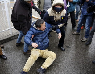 Plainclothes police officers lift a supporter of China's rights lawyer Pu Zhiqiang who was pushed to the ground by police officers near a court where Pu's trial is being held, in Beijing