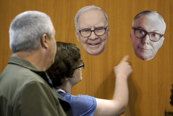 Berkshire Hathaway shareholders look at photos of Berkshire CEO Warren Buffett and vice-chairman Charlie Munger at the Berkshire-owned Fruit of the Loom booth at the shareholder's shopping day in Omaha