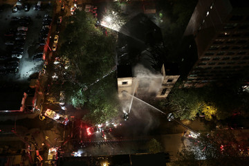 Firemen spray water at the burned Beth Hamedrash synagogue in New York