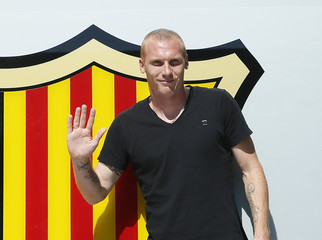French soccer player Jeremy Mathieu waves next to a giant logo upon his arrival at FC Barcelona's offices in Barcelona