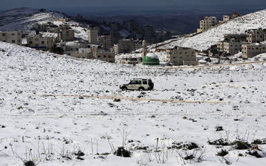 Palestinian drives his car through snow following a snow storm on Mount Jerzim near the West Bank city of Nablus