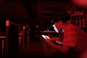An employee at a fast-food restaurant in a shopping mall uses her mobile phone during a power outage that affected several areas in the country, in San Juan