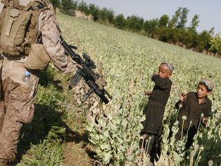 Afghani children look at a U.S. Marine as he patrols a poppy field in the area of Karez-e-Sayyidi, near Marjah district, Helmand province