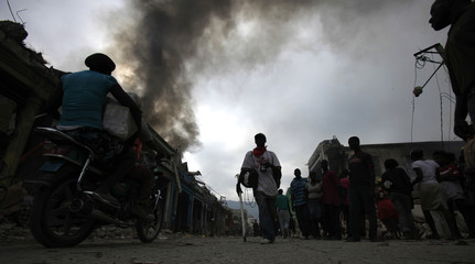 People walk near a burning store in downtown Port-au-Prince