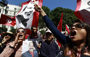 A demonstrator holds portrait of the late Tunisian opposition leader Chokri Belaid as others wave flags and poster of slain opposition leader Mohamed Brahmi at an event commemorating the Feast of Martyrs at Avenue Habib Bourguiba in Tunis
