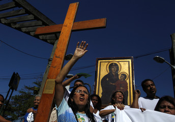 Faithfuls sing in front of the World Youth Day symbols during a visit to the Vidigal slum in Rio de Janeiro