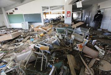 A photographer walks among debris in a classroom inside the tsunami-hit Okawa Elementary School in Ishinomaki