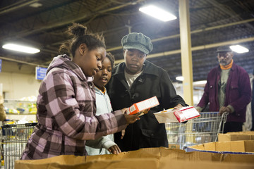 Miller compares items with her daughters at St. Vincent de Paul food pantry in Indianapolis