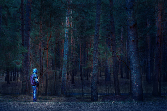 Kid boy alone standing in forest at night time