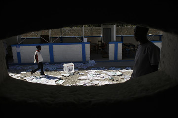 Haitians walk over electoral materials after frustrated voters destroyed them during a protest at a voting center in Port-au-Prince