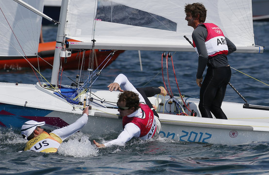 Gold medallists Australia's Mathew Belcher and Malcolm Page and silver medallists Argentina's Lucas Calabrese and Juan de la Fuente celebrate as they cross the finish line in the men's 470 sailing class during the medal race at the London 2012 Olympic Game