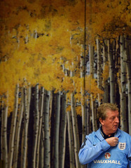 England's manager Roy Hodgson walks past a photo backdrop of an autumn scene as he arrives for a news conference, ahead of their 2014 World Cup qualifying soccer match against Montenegro, at the team hotel near London