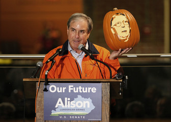 Congressman Yarmuth holds up a pumpkin with the face of U.S. Senate minority leader McConnell carved in it during a campaign rally for Democratic Senate candidate Grimes in Louisville