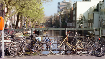 Green tranportation of Amsterdam, Netherland. Bikes parking over canal bridge