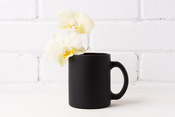 Black coffee mug mockup with soft yellow orchid
