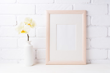 Wooden frame mockup with soft yellow orchid in vase