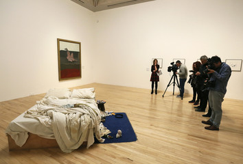 "Members of the media film and photograph British artist Tracey Emin's conceptual artwork ""My Bed"" at Tate Britain in London"