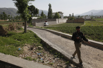 The compound where al Qaeda leader Osama bin Laden was reported killed is seen in the background as a policeman walks past on a nearby road in Abbottabad Pakistan