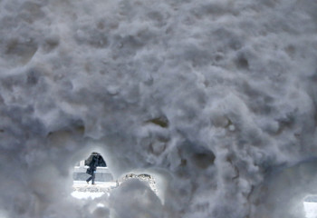 A person walks past a snow covered bus shelter in downtown Chicago