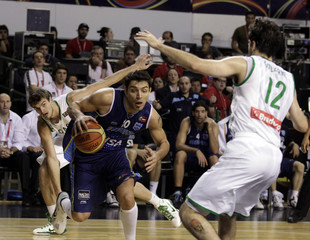 Argentina's Delfino goes to the basket under pressure of Brazil's Splitter and Giovannoni during their FIBA Americas Championship basketball game in Mar del Plata